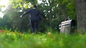 Man i dräkt som lämnar hans fall på gräs och kör lyckligt in i skogen, frihet royaltyfri fotografi