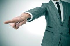 Man i dräkt som pekar med fingret utfarten arkivbild
