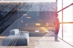 Man i dräktblickar i minimalist vardagsrumfönster royaltyfri fotografi