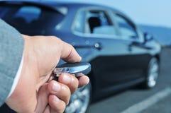 Man i dräkten som öppnar hans bil med kontrollfjärrkontrolltangenten Arkivfoton