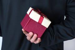 Man i dräkten som rymmer den röda rosa gåvaasken bak hans baksida royaltyfri bild