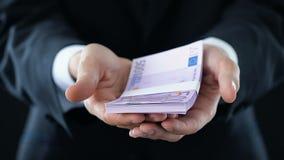 Man i dräkthälerigrupp av europengar, för kassa händer in närbild, ekonomiskt stöd lager videofilmer