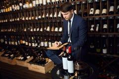 Man i ellegant moderiktig dräkt som ner skriver information om vinprodukt royaltyfri foto