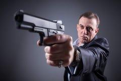 Man i en affärsdräkt med ett vapen Arkivfoton