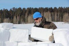 Man i en blå hatt och solglasögon som bygger en igloo från snökvarter i vinter royaltyfri foto