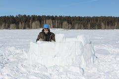 Man i en blå hatt och solglasögon som bygger en igloo från snökvarter i vinter royaltyfri fotografi