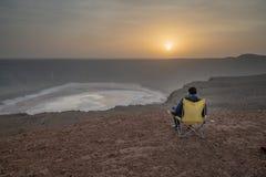 Man i en campa stol på en vulcanic krater under den soluppgångAl Wahbah krater i Saudiarabien royaltyfri fotografi