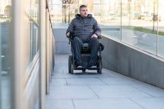 Man i en elektrisk rullstol genom att anv?nda en ramp royaltyfri foto