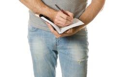 Man i en handnotepad och penna Arkivfoto