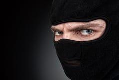 Man i en maskering på svart bakgrund Arkivfoto