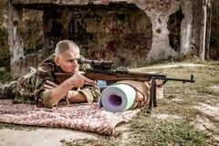 Man i en militär likformig med ett vapen Royaltyfria Foton