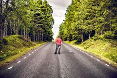 Man i en röd skjorta som ser ner en asfaltväg arkivbild