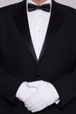 Man i en smoking som ha på sig vithandskar. arkivfoto