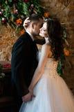 Man i en svart dräkt som kysser hans kvinna arkivfoton