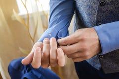 Man i en tux som fixar hans cufflink royaltyfria foton