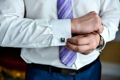Man i en tux som fixar hans cufflink arkivbilder