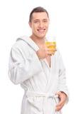Man i en vit badrock som rymmer orange fruktsaft Fotografering för Bildbyråer