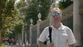 Man i en vit skjorta och mörka exponeringsglas, med en svart ryggsäck på hans skuldra arkivfilmer