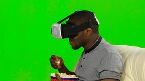 Man i en VR-maskering som håller ögonen på en film och äter popcorn grön skärm arkivfilmer