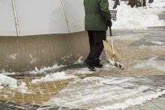Man i enhetlig rengörande snö med en skyffel royaltyfria bilder