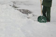 Man i enhetlig rengörande snö med en skyffel arkivfoton