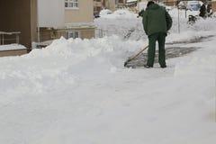 Man i enhetlig rengörande snö med en skyffel royaltyfria foton