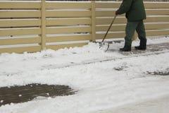 Man i enhetlig rengörande snö med en skyffel royaltyfri foto