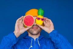 man i ett blått omslag för sport90-talstil och en gul hatt med squishy vattenmelon- och ananasleksaker fotografering för bildbyråer