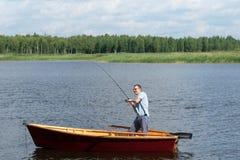 Man i ett fartyg som fiskar på en flod i skogen arkivfoto