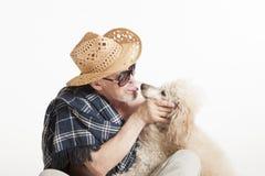Man i ett hattsammanträde med en pudel Fotografering för Bildbyråer
