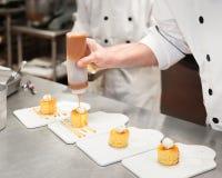 Man i ett kök som duggar karamellsås på små kakor som överträffas med kräm royaltyfria bilder