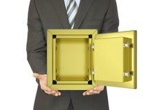 Man i ett öppet guld- kassaskåp för dräktinnehav Arkivbild