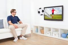 Man i exponeringsglas som 3D håller ögonen på fotboll på TV Royaltyfri Bild