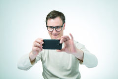 Man i exponeringsglas som fotograferas av smartphonen Arkivfoton