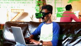 Man i faktisk skyddsglasögon genom att använda en bärbar dator stock video