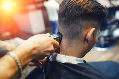 Man i frisersalongen Stäng sig upp av en ung vit grabb medan bitande hår för frisören i friseringsalongen arkivfoto
