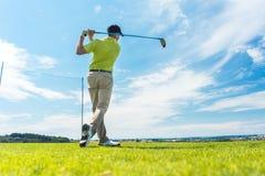 Man i fullföljandepositionen av en körande gunga, medan spela golf Royaltyfria Bilder