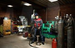 Man i garaget, med svetsning för flammabränninggas Arkivbild