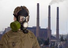 Man i gasmask mot bakgrunden av det industriella landskapet Arkivfoton