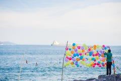 Man i gräsplan som binder färgrika ballonger för att skjuta Royaltyfria Foton