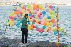 Man i gräsplan som binder färgrika ballonger för att skjuta Fotografering för Bildbyråer