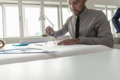 Man i grå skjorta och smokingen som arbetar på ritning Royaltyfria Bilder