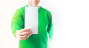 Man i grönskatröjaleende, reklamblad för handinnehavmellanrum A4, D royaltyfri foto