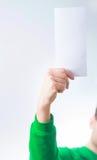 Man i grönskatröjaleende, reklamblad för handinnehavmellanrum A4, D arkivbild
