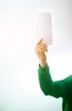Man i grönskatröjaleende, reklamblad för handinnehavmellanrum A4, D royaltyfri fotografi