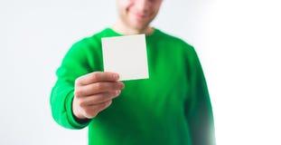 Man i grönskatröjaleende, reklamblad för handinnehavmellanrum A4, D royaltyfria bilder