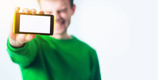 Man i grönskatröjaleende, smart telefon för handinnehav med royaltyfri fotografi