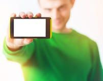 Man i grönskatröjaleende, smart telefon för handinnehav med arkivfoto