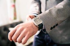 Man i Grey Jacket Adjusting hans fyrkantiga klocka på middagar royaltyfri fotografi