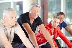 Man i grupp av pensionärer som rotera i idrottshall Royaltyfri Foto